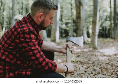 A logger with an ax in the forest. Bearded logger.
