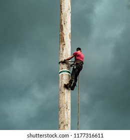 Logger Climbing Wood Pole With Red Shirt