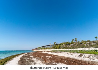 Loggerhead Beach at Bahia Honda State Park on Big Pine Key in Florida. The washed up sea grass prevents beach erosion and you cannot remove it. Bahia Honda old bridge in background.