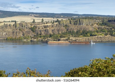 Logging barge on the Columbia River Gorge carrying logs and sawdust.  Oregon.