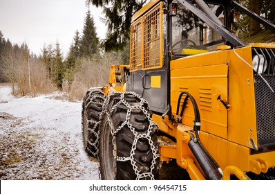 Logging machine giant wheels equipped with snow chains. Winter scenery. HDR