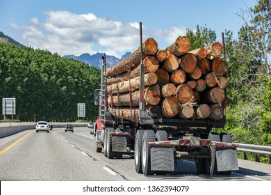 Logging truck with heavy load traveling fast on highway