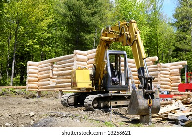 Loghouse under construction with an excavator in front of it