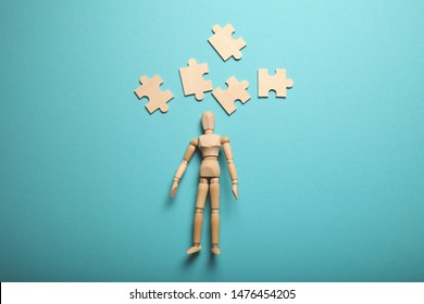 Logical difficulties, confusion in thoughts, puzzles above the head of wooden figure.