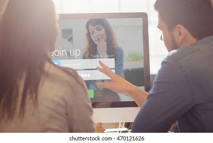 Log-in screen with redheaded woman against graphic designers working at desk in the office