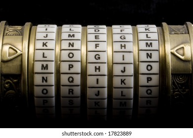 login word set up as a password to combination puzzle box (cryptex) with rings of letters; black background