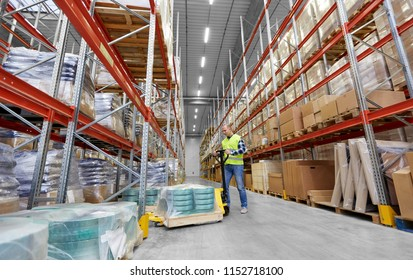 logistic business, shipment and loading concept - male worker with loader working at warehouse