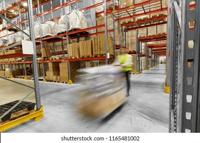 logistic business, shipment and loading concept - motion blurred picture of worker carrying loader with goods at warehouse