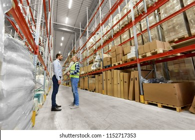 logistic business, shipment and people concept - male worker and businessman with clipboards at warehouse