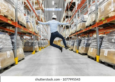 logistic business, success and people concept - happy businessman in helmet jumping at warehouse