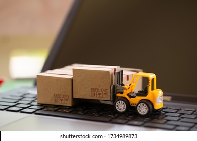 Logistic and cargo freight concept: Fork-lift a truck moves a paper box on notebook keyboard. depicts International freight or shipping service for online shopping.