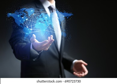 Logistic concept. Man holding virtual world map on dark background