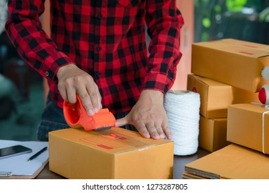logistic, delivery, shipment, people and export concept - happy man in safety vest packing box or parcel with scotch tape at warehouse or mail storage