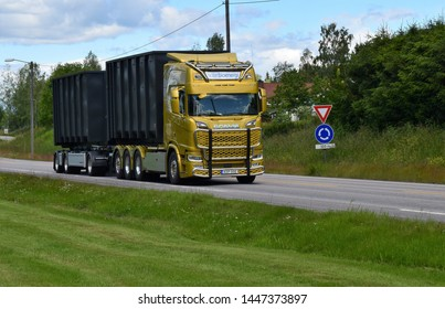 Logistic and transportation yellow Scania truck with Solør Bioenergi sign on the highway road in sunny and summer season - Kongsvinger, Norway (5th july 2019)