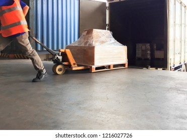 Logistic and warehouse. warehouse loader are dragging the shipment pallet, unloading out of a truck to warehouse.