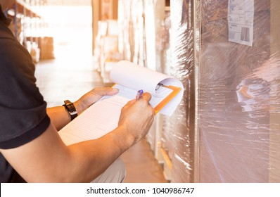 ?Business and Logistic, Warehouse worker hand holding clipboard writing check, inventory of product in large warehouse.