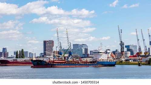 Logistics business. Huge cranes and ships anchored at harbor. International commercial port, city of Rotterdam background, sunny summer day