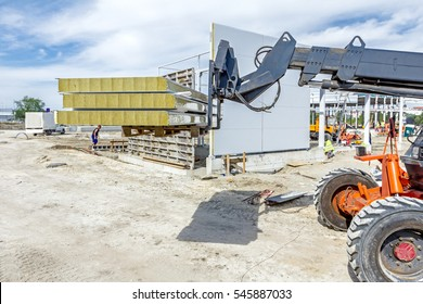 Logistics concept, view on telescopic forklift that is carries composite panel walls at construction site.