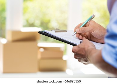 logistics - delivery service man writing documents on clipboard
