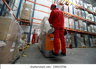 logistics - Goods delivery - two workers working in storehouse with forklift loader