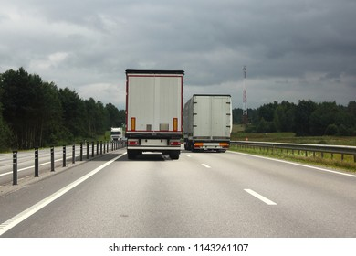 Logistics, international freight by road-two white trucks drive next to the two-lane asphalted country road in the summer day, rear view