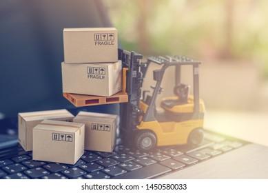 Konzept der Logistik, der Lieferkette und der Zustelldienste: Gabelstapler transportiert eine Palette mit Karton. Die Boxen auf einem Laptop-Computer zeigen eine breite Produktpalette rund um den Globus in der boomenden Zeit des elektronischen Geschäftsverkehrs