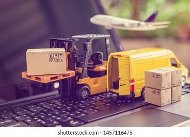 Konzept der Logistik, der Lieferkette und der Zustelldienste: Gabelstapler transportiert eine Palette mit Karton. Van auf einem Laptop-Computer, zeigt eine breite Palette von Produkten rund um den Globus in der beliebten E-Commerce-Zeit
