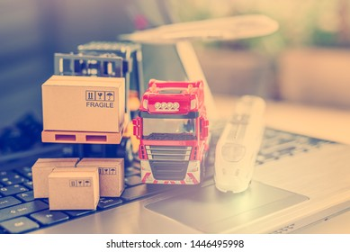 Logistics and supply chain management for online shopping concept : Red truck, air plane, hi-speed train, fork-lift moves a box / cartons on a laptop computer, depicts delivering goods or products