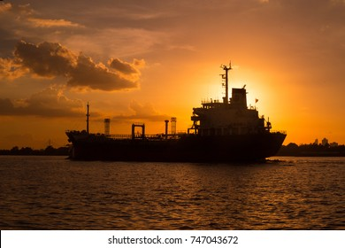 Logistics and transportation of International Container Cargo ship in the ocean at sunset,and silhouette of boat