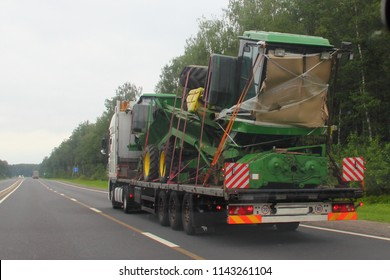 Logistics, transportation of new large-size special equipment (big tractor) on a low-frame three-axle semi-trailer trawl on a two-lane paved country road in the summer day, rear-side view