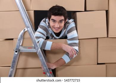 Logistics worker hiding amongst boxes
