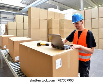 logistics worker - man scans parcels of goods and prepares the dispatch in a company's department store