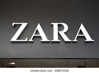 "Logo of famous brand ""Zara"" in Mall of Asia, Manila, Philippines. Editorial registered trademark photo. Spanish brand Zara shiny logo on shop entrance. Fashion mass-market brand name close photo"