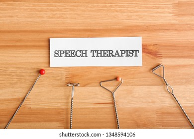 Logopedic probes and paper with text SPEECH THERAPIST on wooden background