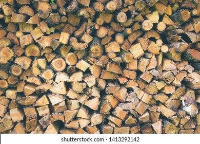 Logs of firewood . Fuel for stove heating. Country life. Wooden firewood stacked wall. Natural wood background. Firewood stacked in several rows