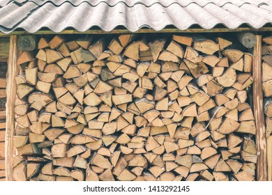 Logs of firewood piled under under the roof of slate. Fuel for stove heating. Country life. Wooden firewood stacked wall. Natural wood background. Firewood stacked in several rows