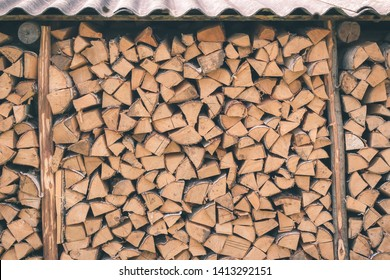 Logs of firewood piled under the roof of slate. Fuel for stove heating. Country life. Wooden firewood stacked wall. Natural wood background. Firewood stacked in several rows