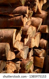 Logs stacked in a woodshed lit by warm sunlight