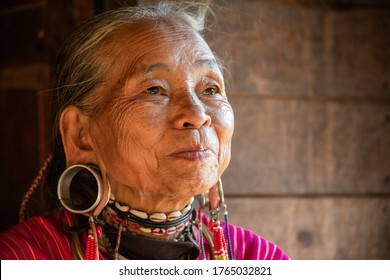 Loikaw, Myanmar - February 2020: Portrait of an old woman from the Kayaw Tribe. Wise old woman wearing decorative beads,  typical earlobe rings and  pink woven traditional costume