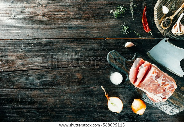 Loin, uncooked and not cutted on rustic board, chopper and spices