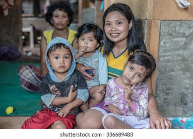 Loko, Sulawesi, Indonesia - August 17, 2014: Indoor portrait of a cute family, two adult women and two babies, in the village of Loko, Mamasa region, West Tana Toraja.