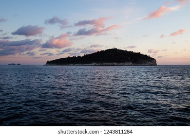 Lokrum island along the coast of Dubrovnik during sunset with purple clouds and deep blue ocean, Croatia