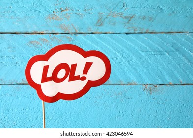 LOL bubble text comic retro sign, in front of wooden background