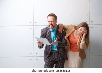 LOL! Watching funny video or reading a joke. Creative work and technology. Young man and woman using tablet computer and laughing against white wall.