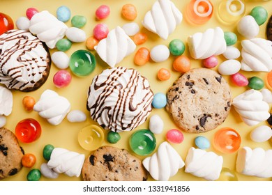 lollipop candy background, confectionery design concept. chocolate cookies, marshmallows, caramel candies on yellow table. sweet food, sugar, dessert backdrop