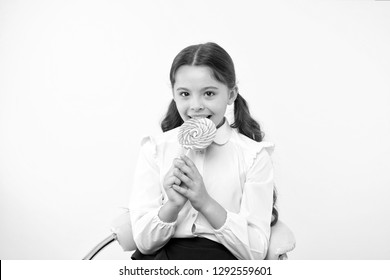lollipop child. child eating lollipop in yellow studio. lollipop child eating candy with happy face. child lick sweet lollipop candy. having fun with candies