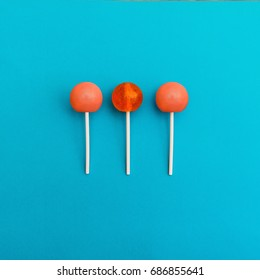 Lollipop Flat lay Minimal concept Three orange round lollipops are lying on a light blue background Trendy bright photo in modern pop art style Top view