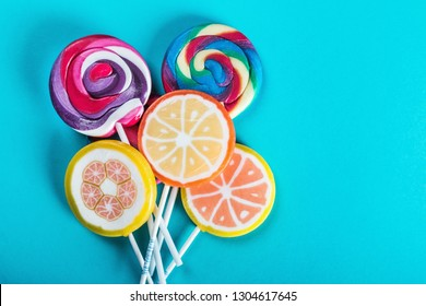 lollipops of different colors on a blue background. sweets and candies