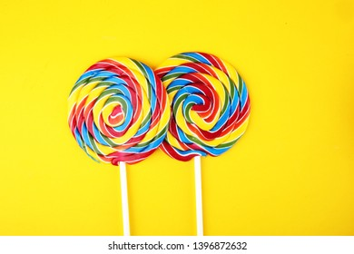 lolly candies with sugar. colorful array of childs lollipops sweets and treats on yellow