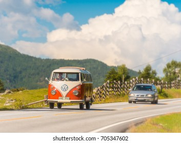 Lom, Norway - July 25, 2013: old VW red and white camper van car on country road in Norway, Europe, Scandinavia